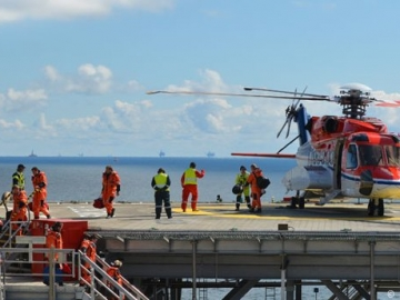 Offshore Oil & Gas Workers Disembark Helicopter On Offshore Platform Helideck